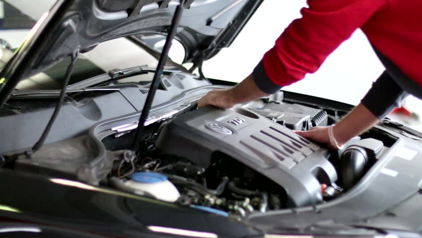 A repairman with a vacuum pump. Diesel engine car reparation and test. A mechanic testing the pressure of a diesel engine.  - HD stock footage clip