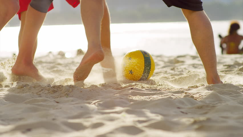 Friends play soccer on the beach in Brazil.
