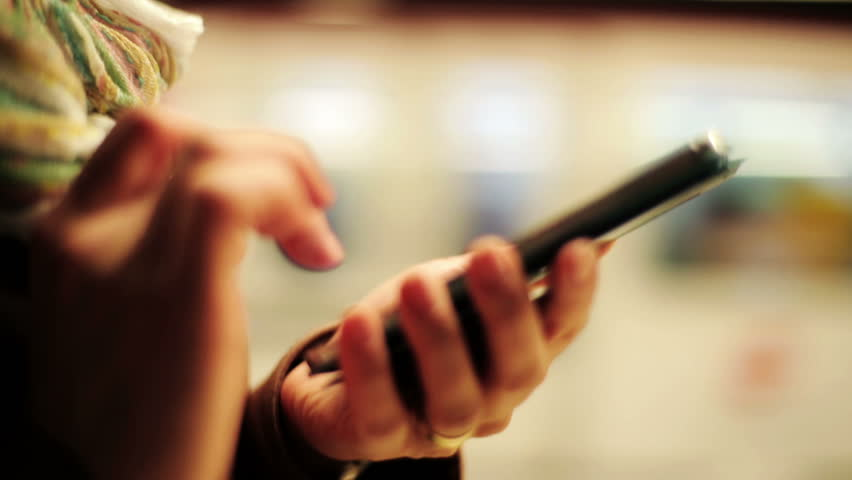 Woman hands texting on smartphone on metro station