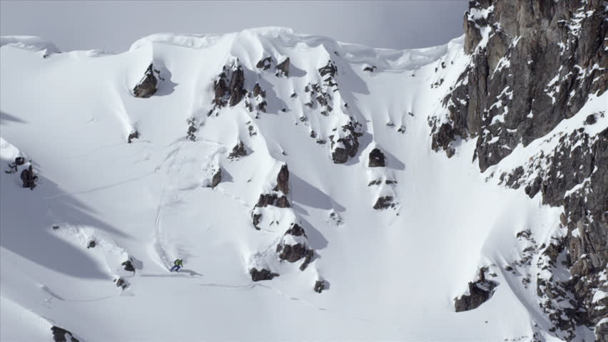 Skier carving a slope, triggers and large avalanche, shows a long range view of it as he manages to outrun it