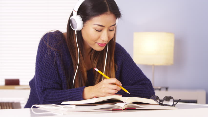 Japanese woman listening to music while doing homework - HD stock footage clip