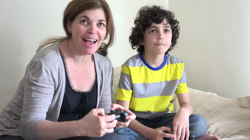 Single Hispanic mother playing or gaming with her child at home, small family of woman and son having fun indoors.