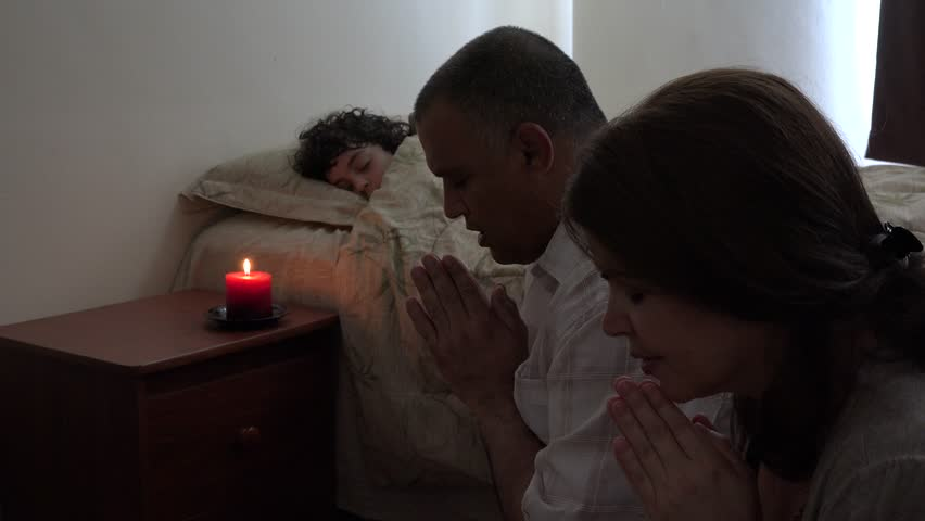 Hispanic Christian family praying for their child in bed, small family on her knees asking for her sick son who is sleeping, reverence,praise,and faith in the healing power of God or Jesus.