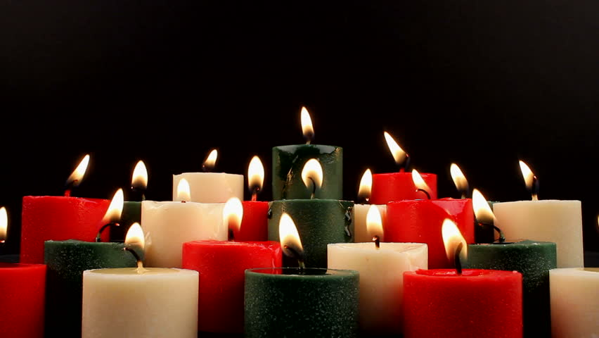 Serene candle background, red, white, green lit, burning pools of melting wax, zoom in. 1080p - HD stock footage clip