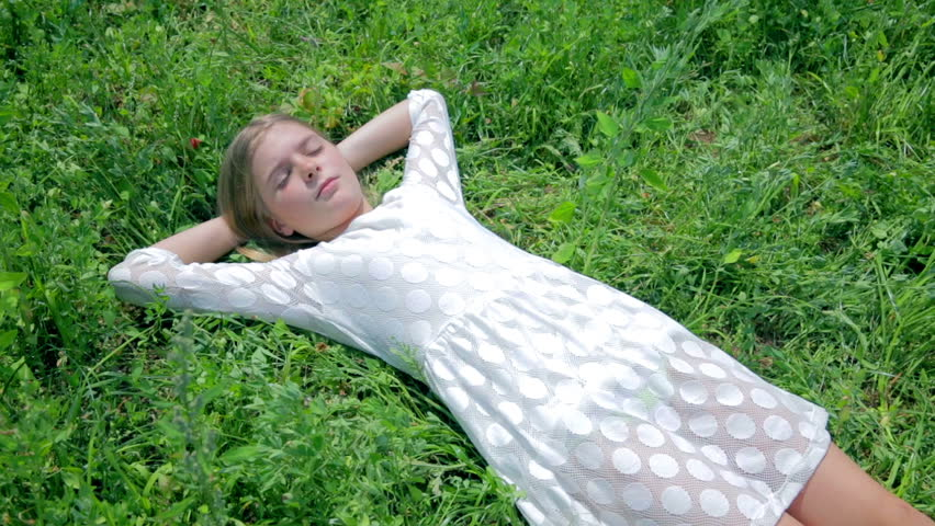 Girl In White Dress Laying In Grass Waking Up Stock