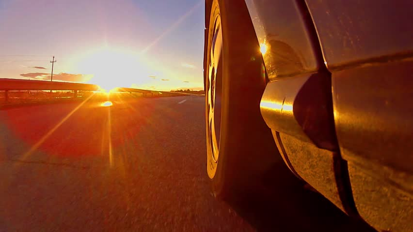 beautiful low angle view of sport car race with sunset rays shining on tire, TIMELAPSE - HD stock video clip