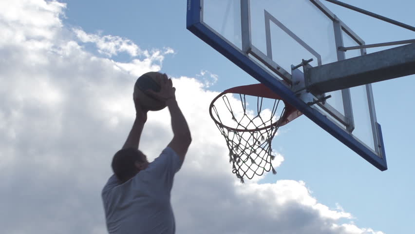Spectacular Low Angle Rearview Shot Of Professional Basketball Player Scoring A Basket By Alley-Oop And Hanging On The Hoop | Shutterstock HD Video #6640535