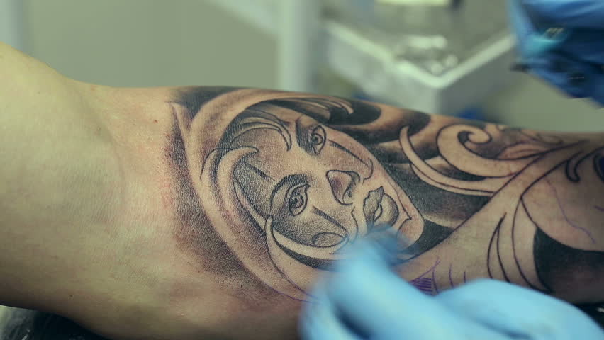 Tattoo artist working man draws on his arm woman 39 s face for Working man tattoo