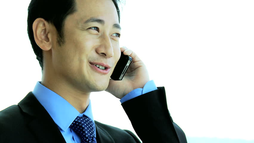 Asian Chinese male advertising executive talking smart phone standing window modern skyscraper overlooking city close up | Shutterstock HD Video #6644891