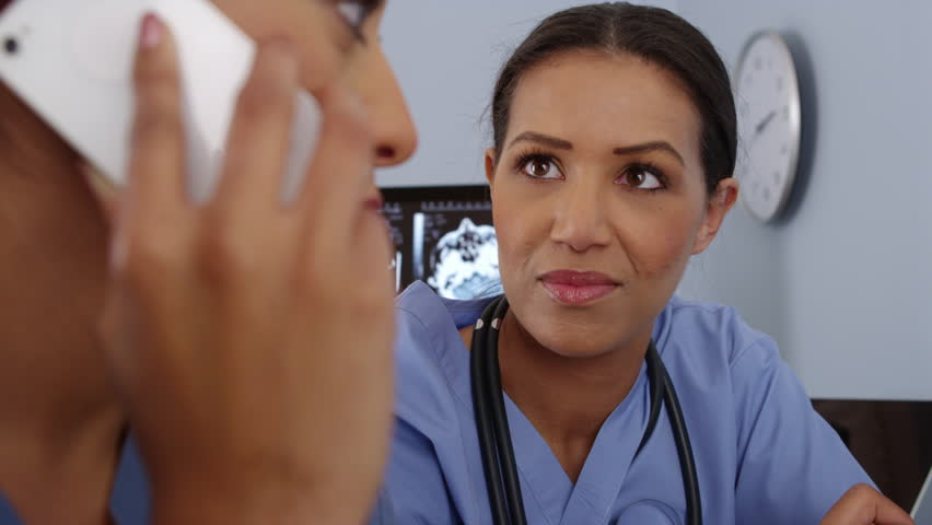 Close up of Hispanic doctor using mobile phone while colleague uses computer