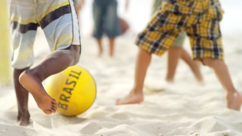 Kids playing soccer on a beach