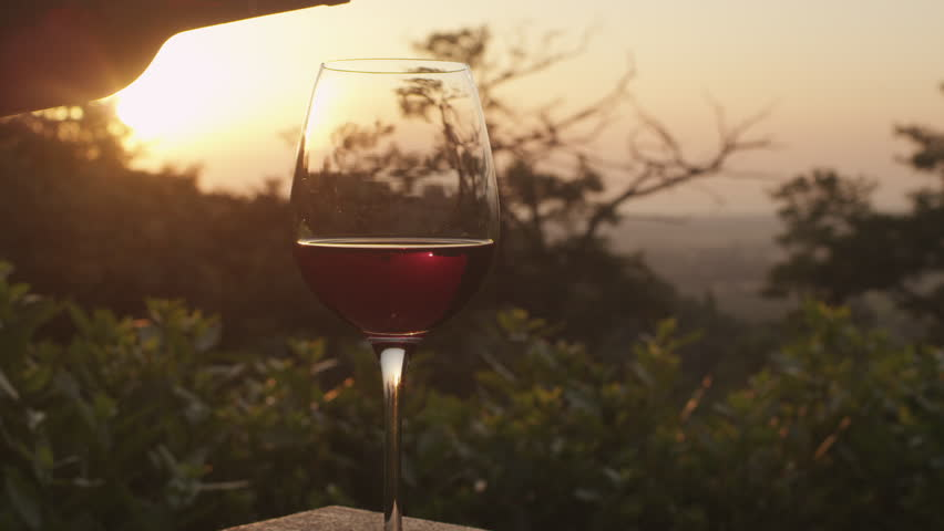 Pouring Wine into Glass at Sunset Time. Shot on RED Digital Camera in 4K , so you can easily crop, rotate and zoom, without losing quality. ProResHQ - Great for editing, color correction and grading. - 4K stock video clip