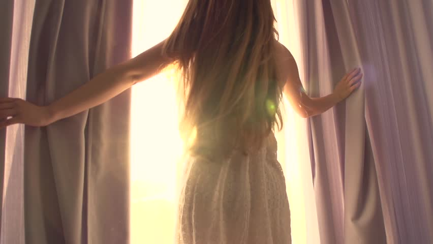 Beauty Girl opens curtains on big window and let the light in the room. Looking out the window. Slow motion video footage full hd 1920x1080. High speed camera shot 240 fps