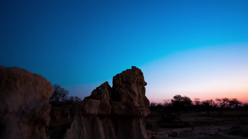 Linear, push-in holy grail timelapse of abstract landscape with eroded rocks while the sun is setting from day to night, while the Milky Way moves into the frame.