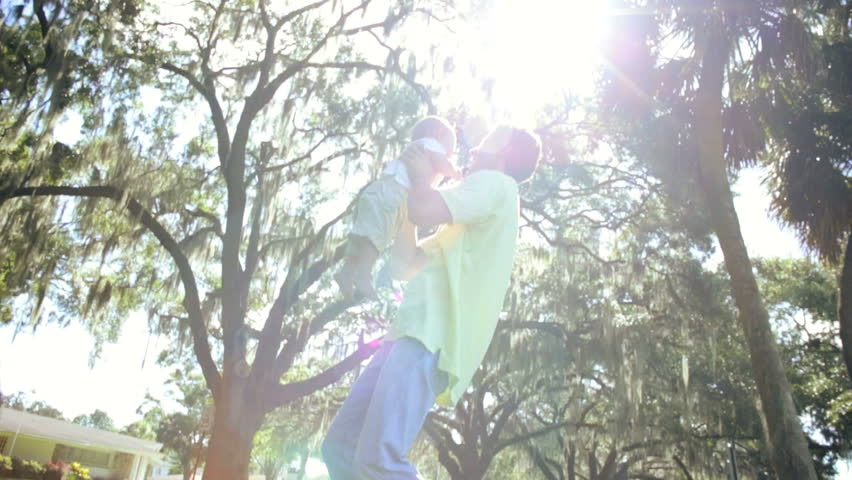 Loving Young Father Holding Baby Son High Outdoors - Healthy young Caucasian baby having fun held high in fathers arms outdoors visit park sun lens flare slow motion - HD stock video clip
