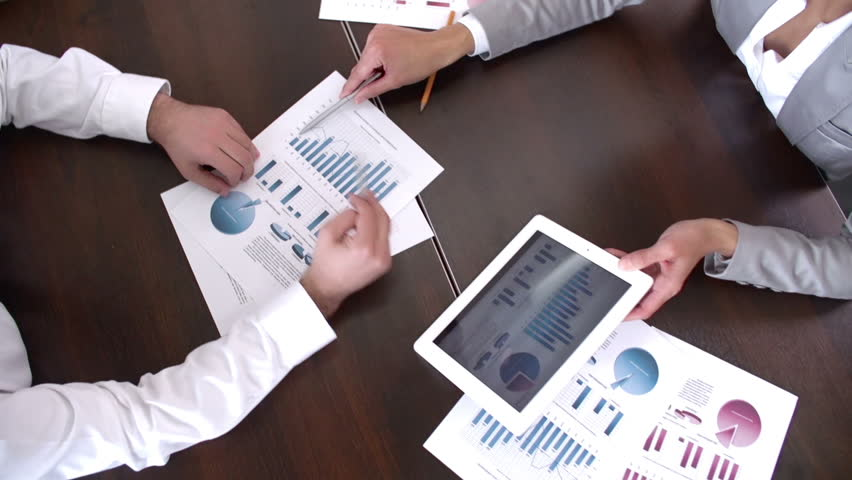 Above view dolly shot of graphic data templates on long table with unrecognizable business people analyzing them | Shutterstock HD Video #6696389