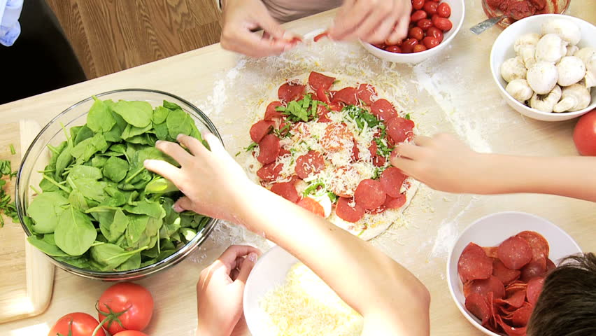 Healthy Caucasian Family Making Pizza Overhead Hands - Overhead view hands no faces Caucasian parents children making healthy living lunch fresh tasty pizza using organic salad vegetables salami