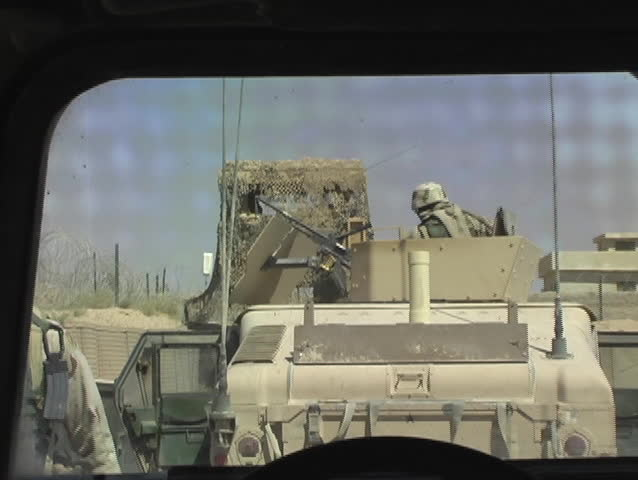 Iraq, Circa, 2005: US soldiers walk by Humvee as turret gunner readies himself in the seat for an upcoming sortie in Iraq, Circa, 2005.
