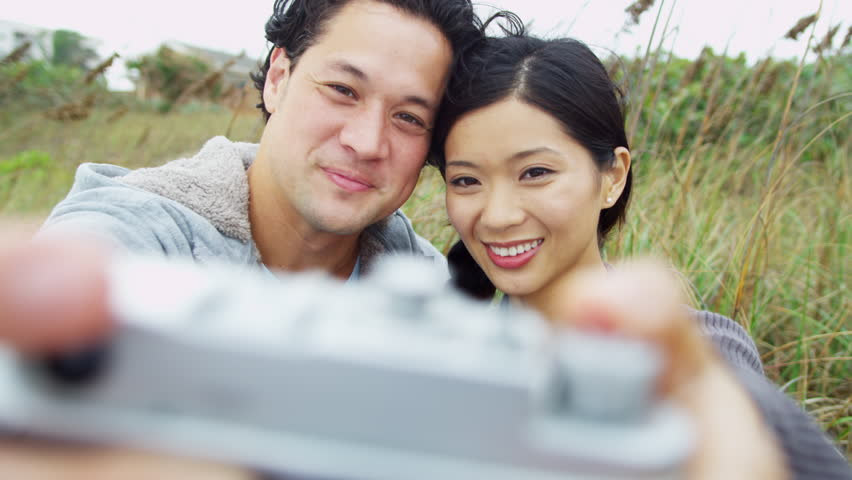 Attractive young Asian Chinese couple head shoulders smiling having fun Fall beach filming self portrait video selfie close up shot on RED EPIC