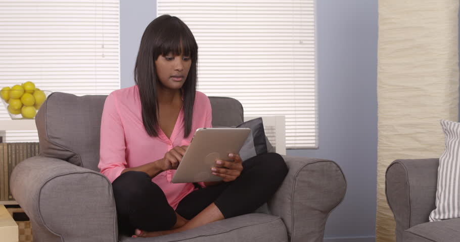 African-American woman using tablet on couch - 4K stock video clip