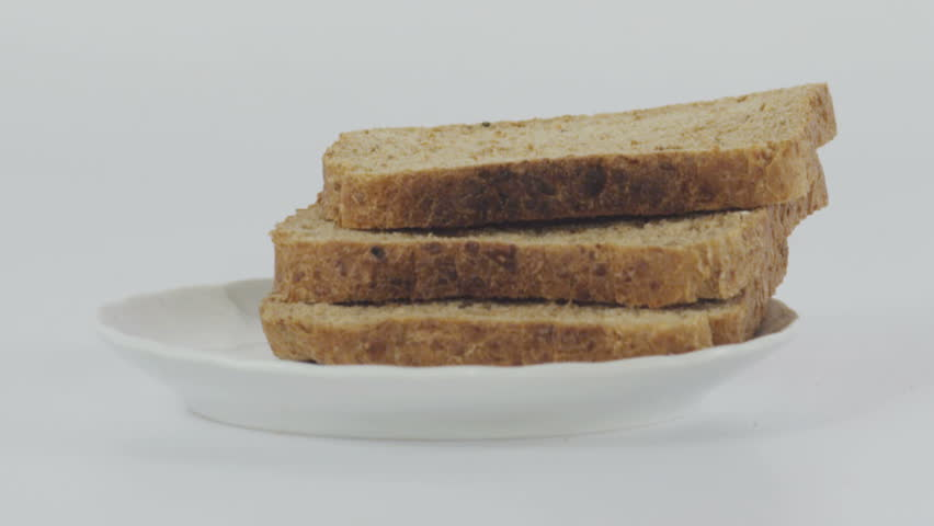 Pieces of bread falling on white surface