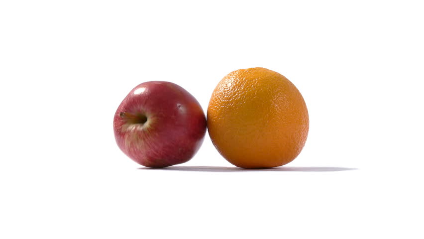"The saying ""Comparing apples and oranges"" means that the contrast between individual items is too great for them to be validly compared. An apple and an orange collide on a white background."