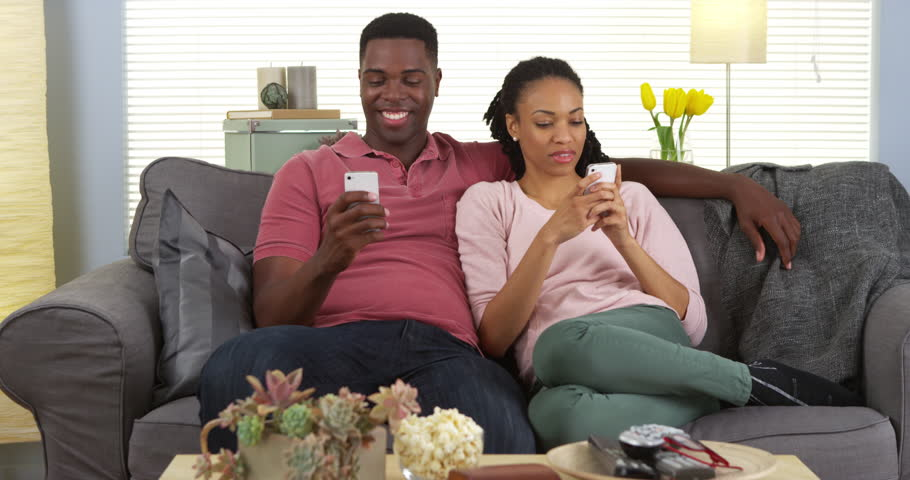 Happy young black couple relaxing on couch using smartphones - 4K stock footage clip