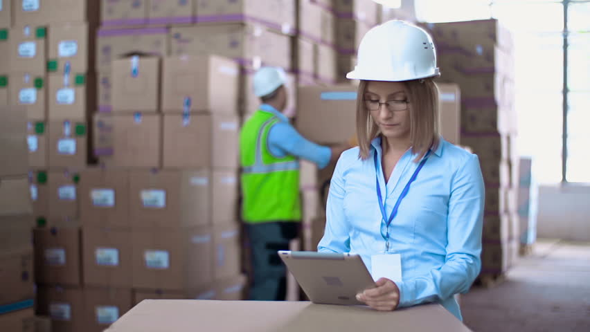 Close up of woman in helmet browsing digital tab while laborer rearranging boxes with merchandise in the background - HD stock footage clip