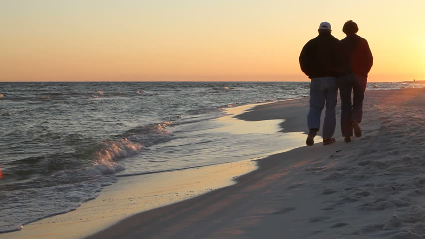 Mature loving couple walk away on the beach at dusk in the winter. They are bundled up for the cold wind. - HD stock footage clip