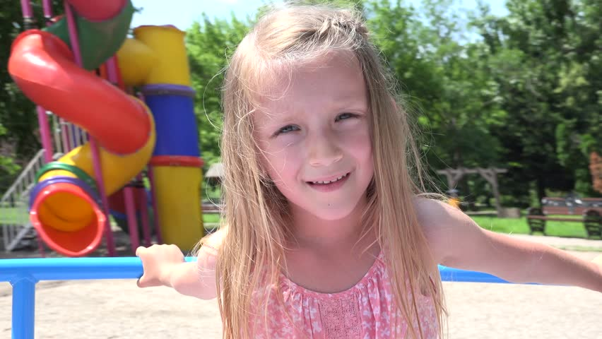 Ultra HD 4K Happy Child Playing at Playground, Portrait of a Little Girl Spinning, Rotating on a Merry-Go-Round in Park, View Caucasian Kid Enjoying Nature, Children Have Fun Outdoor - 4K stock footage clip