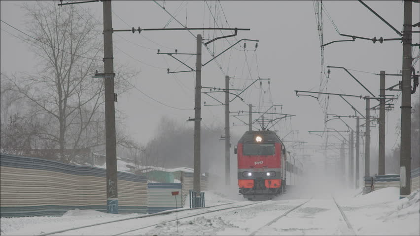 NOVOSIBIRSK, RUSSIA - FEBRUARY 12: Passenger Train passing by lifting snow dust on December 12, 2013 in Novosibirsk, Russia
