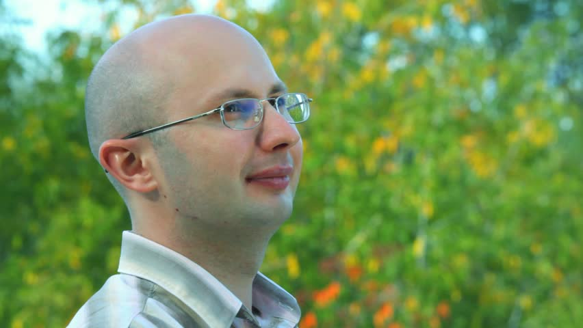 portrait of smiling bald-headed bespectacled man stands against trees in park  - HD stock footage clip