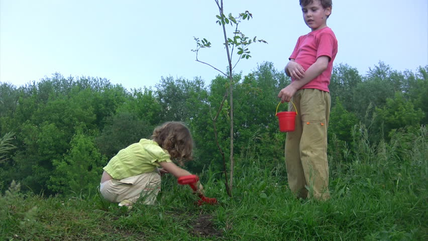 girl with shovel digging, boy with bucket watering young plant