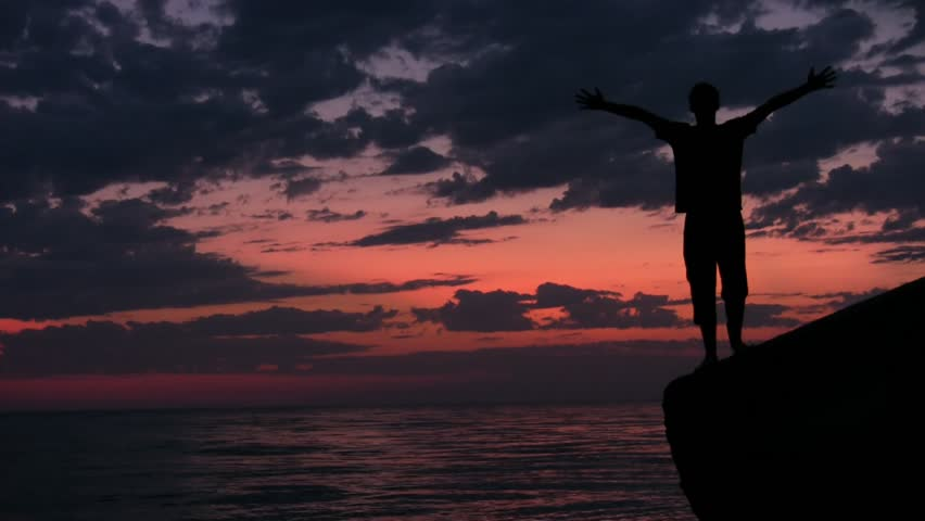 teenager stands with raised hands on rock against sunset sky and sea  - HD stock video clip
