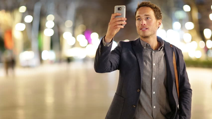 Smart phone Man taking photo with phone at night. Young casual professional business man taking picture with camera phone with flash on smartphone.