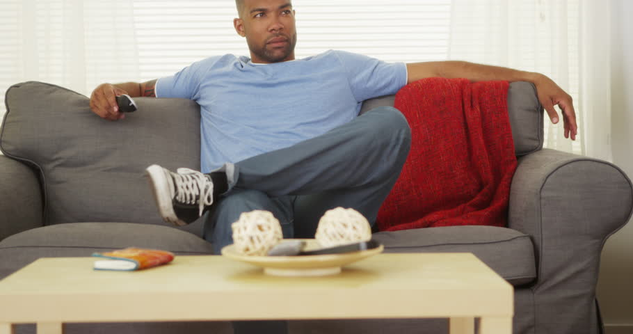 African man sitting on couch watching tv - 4K stock video clip