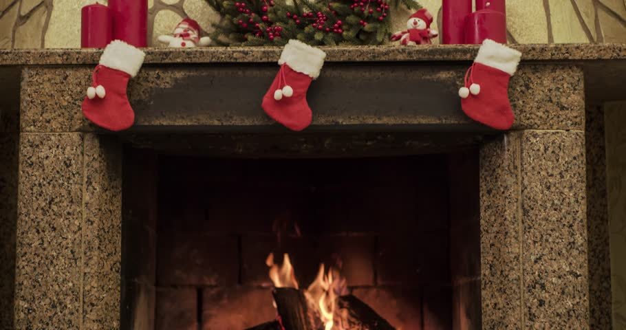 Slow motion fireplace burning. Warm cozy fireplace decorated for Christmas with real wood burning in it. Dolly shot. 4k graded from RAW.