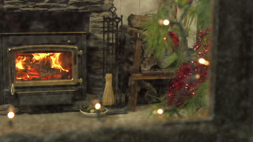 Dolly/pan reveal of beautiful Christmas scene - fire burning brightly as snow falls heavily outdoors