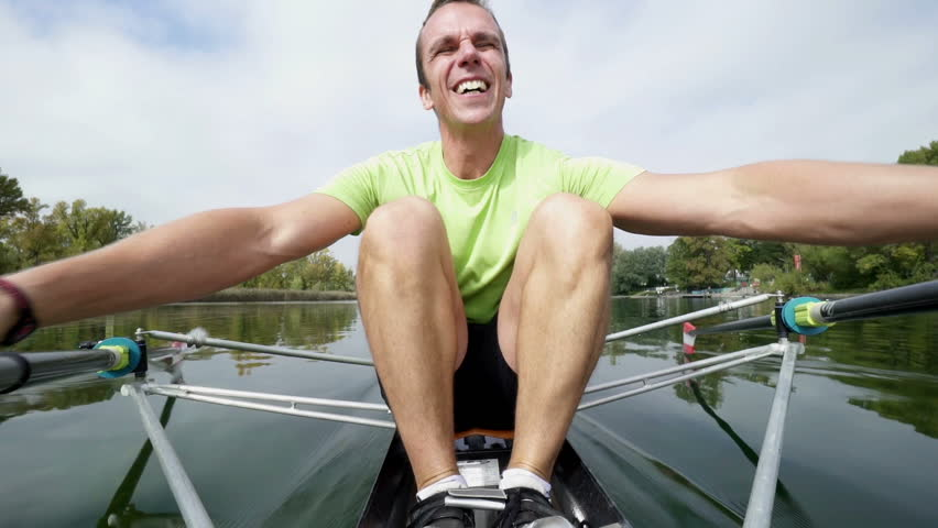 professional single rower in rowing boat on calm river
