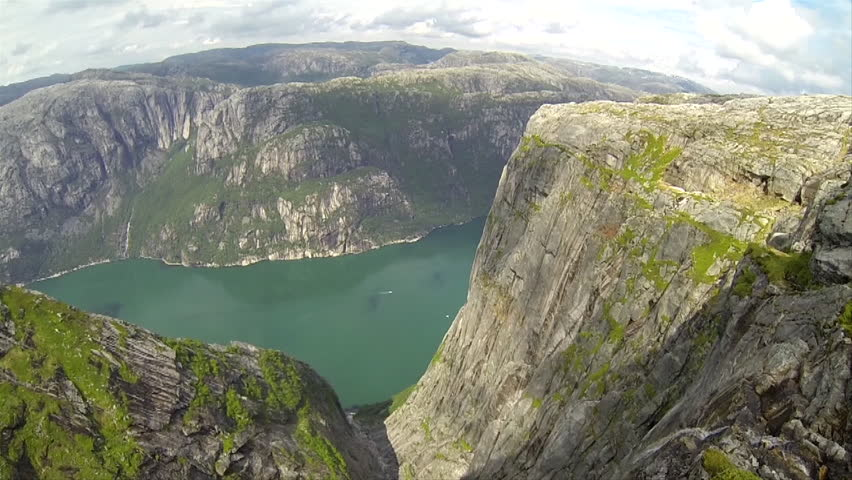 A base jumper in a wingsuit jumps from a cliff before gliding down in the air, a river visible below - HD stock footage clip