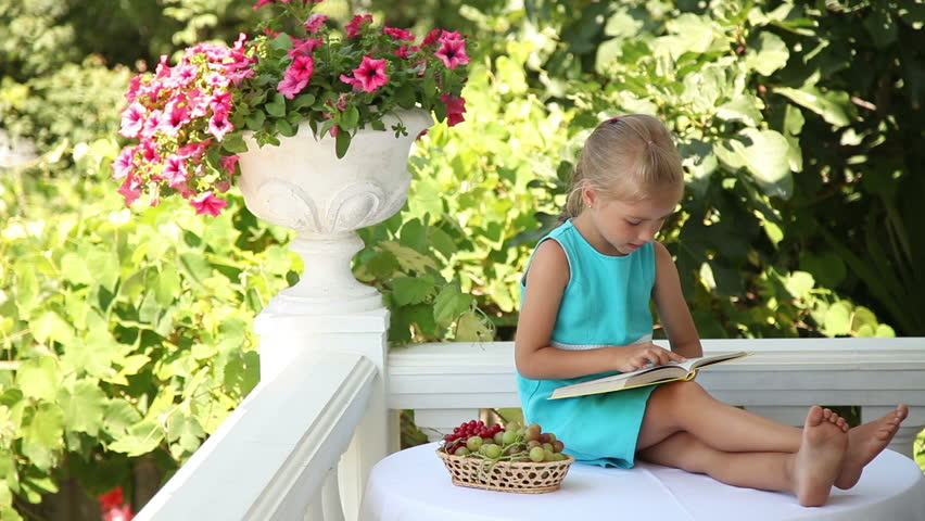 Smiling Little Girl Reading A Book In The Garden She