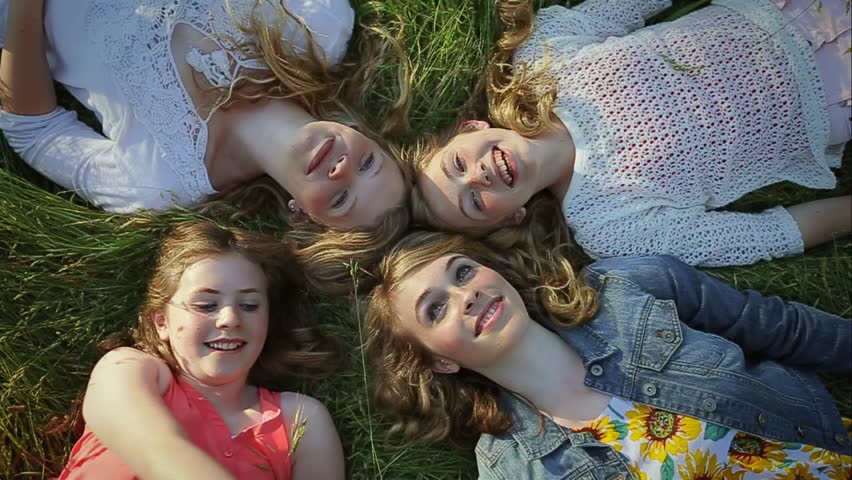 Sisters Lay In Grass, Youngest Points At Sky, They All Look Up Excitedly