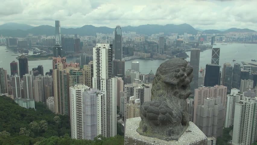 HONG KONG - CHINA, MAY 15, 2012, Pan right of Island Kowloon, Pearl River and leon statue with skyscrapers in cloudy day