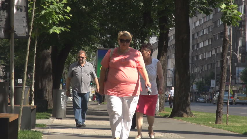 BUCHAREST, ROMANIA - 20 OCTOBER, 2014 Fat woman walk on crowded street, pedestrians move downtown in green alley