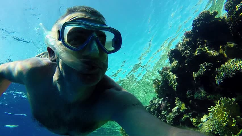 Summer fun, sea, recreation, holiday, vacation, water sport. Man swimming underwater, apnea diving, snorkeling, coral reef with GoPro, Go Pro, Go-Pro video camera, Marsa Alam, Red Sea, Egypt. 2of16