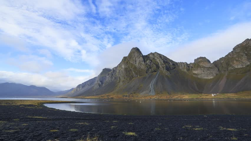 Hvalnes Nature Reserve on the south east coast of Iceland, time-lapse of clouds over a black stone beach and swans.