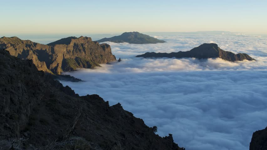 View above waves of clouds moving in the ancient volcano caldera on La Palma, Canary Island, as the sun sets.