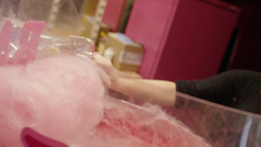 Slow motion close up of server spinning cotton candy at carnival / Paris, France