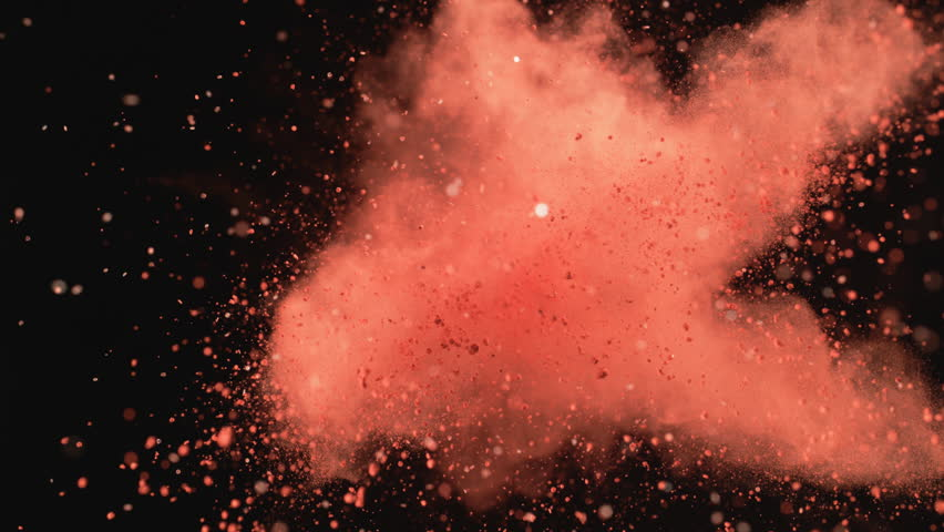 Red powder/particles fly after being exploded against black background. Shot with high speed camera, phantom flex 4K. 4K 30fps. Slow Motion.