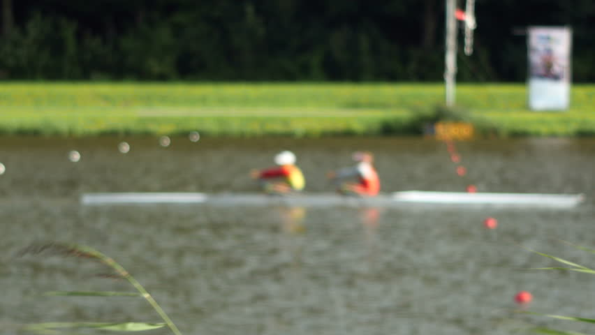 A boat with 2 rowers passes the finish line. Focus on reed in foreground, rowers soft focus. Sunny. Medium shot.